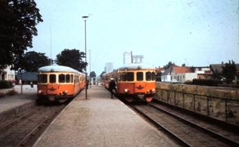 Två orange-röda rälsbussar möts