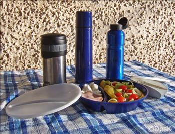 Bild på med olika bra matlådekärl. Tredelad tallrik med sallad, dressing och fårost, matthermos, drickaflaska och kaffethermos.