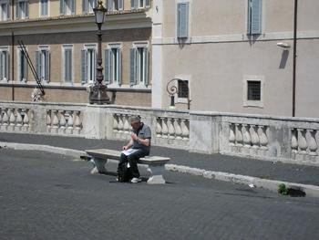 Turist sitter på en bänk och läser kartan