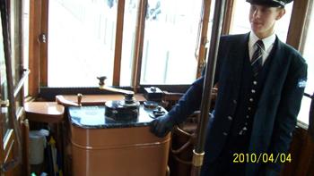 Bilden: Koduktören står bredvid utgången på spårvagnen