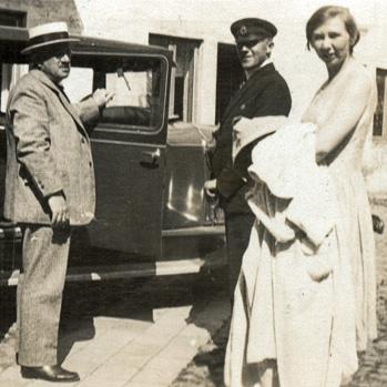 Tre personer framför bilen
